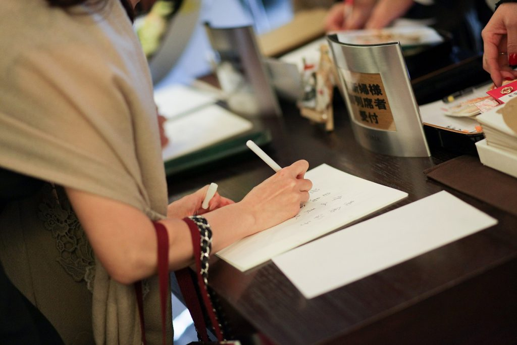 結婚式の受付で芳名帳を書く
